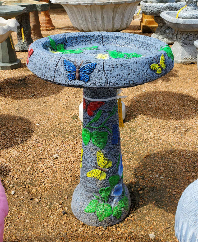 Multicolored cement birdbath with a butterfly motif.